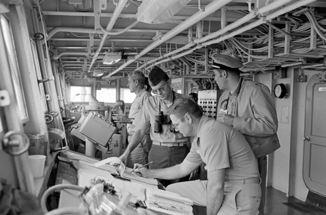 Rear Admiral Frederick F. Palmer, rear, Commander Amphibious Group Two, talks to crewman on the bridge of the amphibious command ship USS MOUNT WHINTEY (LCC 20) while en route to participate in the allied Exercise TEAM WORK '76. The MOUNT WHITNEY is serving as flagship during the exercise scheduled for September 15-24
