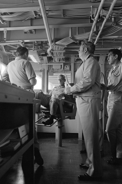 Rear Admiral Frederick F. Palmer, seated, Commander Amphibious Group Two, talks to crewman on the bridge of the amphibious command ship USS MOUNT WHITNEY (LCC 20) while en route to participate in the allied Exercise TEAM WORK '76. The MOUNT WHITNEY is serving as flagship during the exercise scheduled for September 15-24