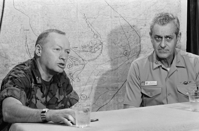 Rear Admiral Frederick F. Palmer, Commander, US Amphibious Group Two, and a Marine Brigadier General hold a briefing aboard the amphibious command ship USS MOUNT WHITNEY (LCC 20) while en route to participate in the allied Exercise TEAM WORK '76. The MOUNT WHITNEY is serving as flagship during the exercise scheduled for September 15-24