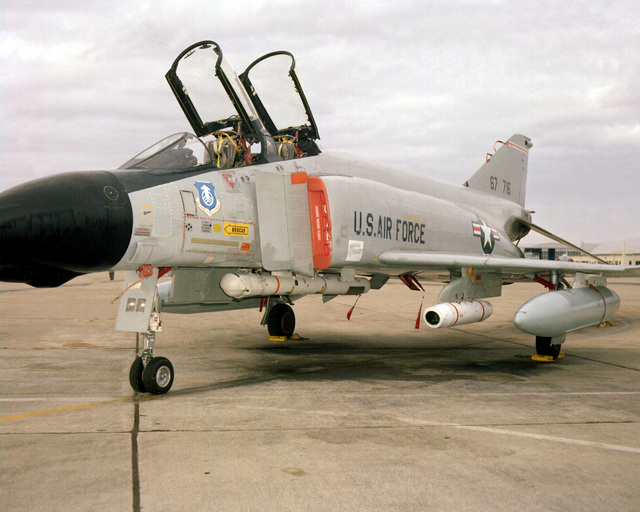A left front view of an F-4D Phantom II aircraft parked on the flight line. The Phantom is equipped with a camera pod on the left wing and a Pave Spike laser target designator pod on the fuselage