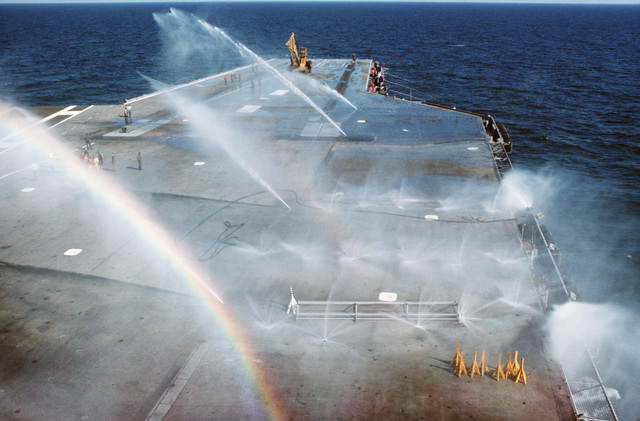 Sea water spray from the flight deck washdown system covers the deck of the aircraft carrier USS AMERICA (CV 66)
