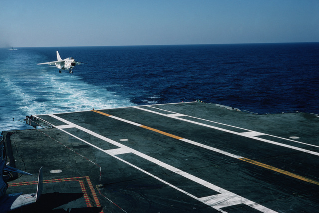 An A-7E Corsair II aircraft approaches the stern of the aircraft carrier USS AMERICA (CV 66) for a landing