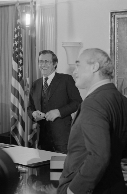 The Honorable Donald H. Rumsfeld, U.S. Secretary of Defense, back, shares a light moment with Martin Agronsky, foreground, from the Public Broadcasting Service (PBS) before an interview at his office at the Pentagon, Washington, D.C., on Nov. 3, 1976. OSD Package No. D-1998-OSD-76-110014 (PHOTO by Robert D. Ward, CIV) (Released)