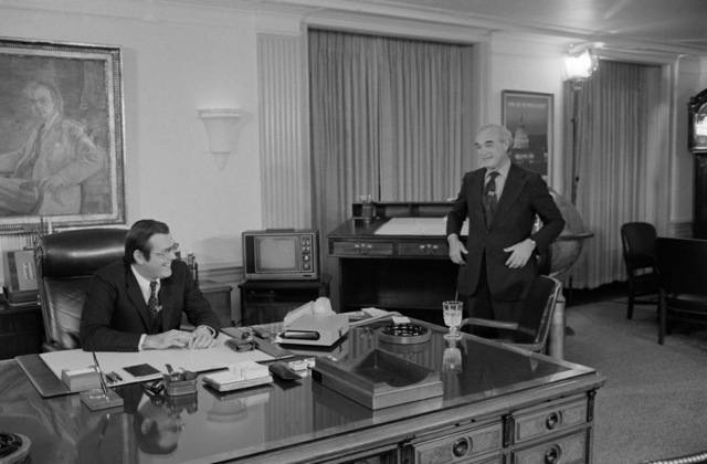 The Honorable Donald H. Rumsfeld, U.S. Secretary of Defense, left, shares a light moment with Martin Agronsky, right, from the Public Broadcasting Service (PBS) before an interview at his office at the Pentagon, Washington, D.C., on Nov. 3, 1976. OSD Package No. D-1998-OSD-76-110014 (PHOTO by Robert D. Ward, CIV) (Released)