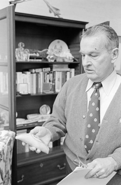 The Honorable William P. Clements, Jr., U.S. Deputy Secretary of Defense, shows one of a souvenir display from a bookshelf inside his office at the Pentagon, Washington, D.C., on Nov. 15, 1976. OSD Package No. D-1998-OSD-76-110016 (PHOTO by Ron Hall, CIV) (Released)