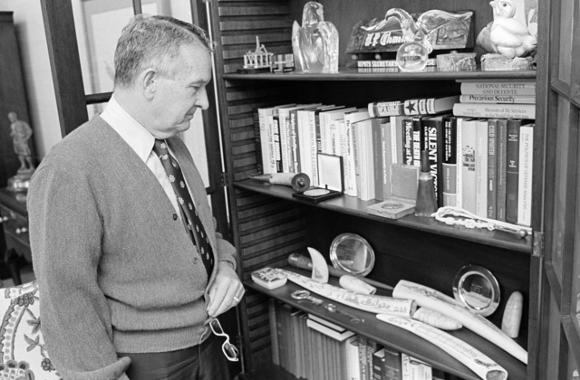 The Honorable William P. Clements, Jr., U.S. Deputy Secretary of Defense, shows some of his souvenir displays on a book shelf inside his office at the Pentagon, Washington, D.C., on Nov. 15, 1976. OSD Package No. D-1998-OSD-76-110016 (PHOTO by Ron Hall, CIV) (Released)