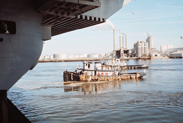 A port view, framed by the stern of the aircraft carrier USS AMERICA (CV 66), of the medium harbor tug DAHLONEGA (YTB 770), partially hidden behind NAHASHO