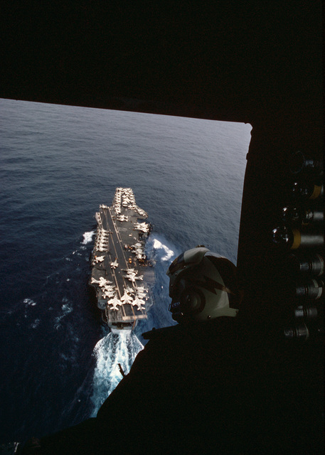 A crewman looks out the cargo door of his aircraft to observe the aircraft carrier USS AMERICA (CV 66) underway below