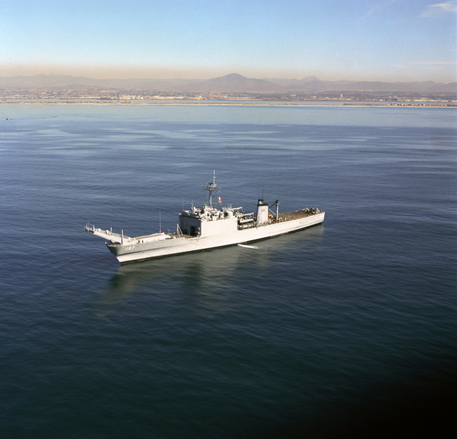 A port bow view of the tank landing ship USS TUSCALOOSA (LST 1187) anchored off the Silver Strand, San Diego, California