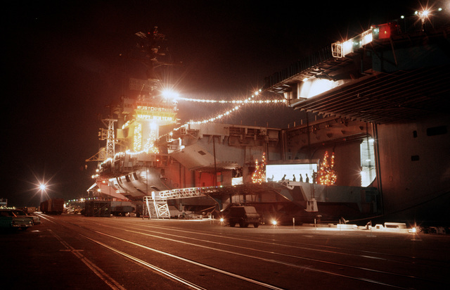 Christmas lights illuminate the aircraft carrier USS AMERICA (CV 66) while the ship is in port
