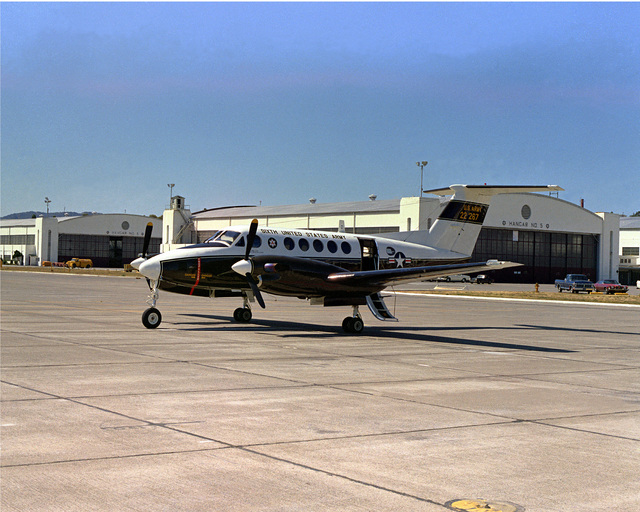 A Beechcraft C-12 Huron (the military designation for the Beechcraft Super King Air 200) sits in front of Hanger 5 at the Presidio of San Francisco