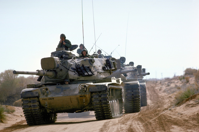 A convoy of M-60 main battle tank moves down a road during a training exercise