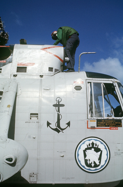 A helicopter maintenance technician inspects a Brazilian navy SH-3D Sea King helicopter parked aboard the aircraft carrier USS AMERICA (CV 66) while underway off the coast of Rio de Janiero
