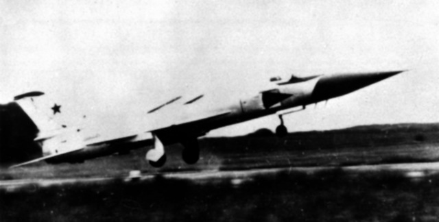 A left side view of a Soviet Su-15 Flagon-B fighter aircraft landing on a runway. (Substandard image)