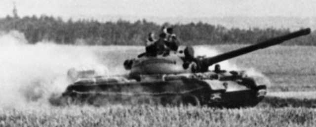 A right side view of a moving Soviet T-62 medium tank. (Substandard image)