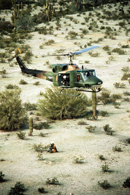 A UH-1 Iroquois helicopter, hovering low over the desert, prepares to pick up a crewman with a rescue harness. The helicopter is participating in combat rescue training exercises