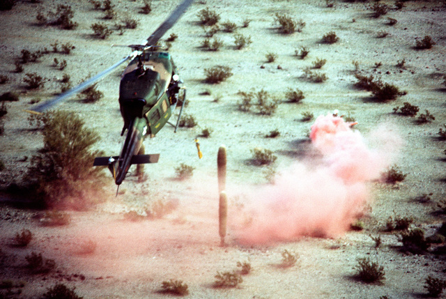 A UH-1 Iroquois helicopter prepares to pick up a crewman marking his position with a red smoke flare. The UH-1 is participating in combat rescue training exercises