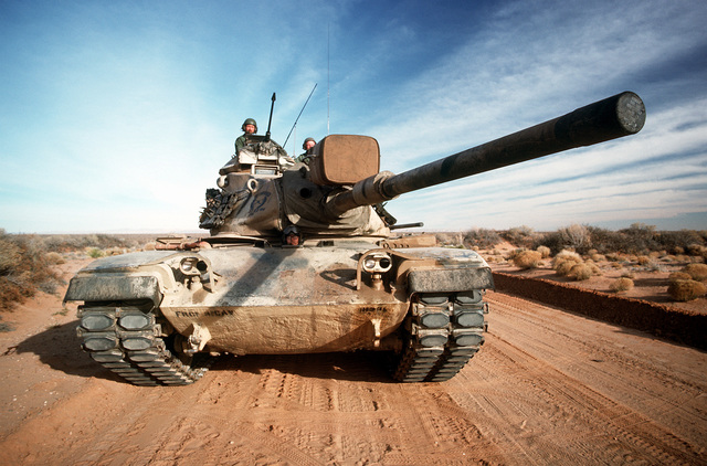 An M-60 main battle tank moves down a road during a field training exercise