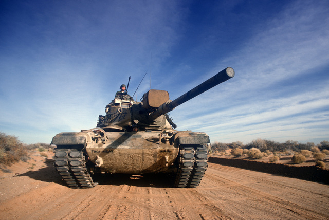 An M-60 main battle tank moves down a road during a training exercise