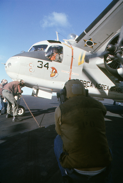 Brazilian flight deck crewmen remove tie-down chains on a Brazilian S-2G Tracker aircraft aboard the aircraft carrier USS AMERICA (CV 66) while underway off the coast of Rio de Janiero