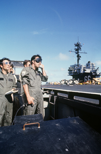 Brazilian landing signal officer (LSO) talks to a pilot by radio during aircraft recovery aboard the aircraft carrier USS AMERICA (CV 66) while underway off the coast of Rio de Janiero.  The LSO is manipulating a device controlling the Fresnel Lens Optical Landing System