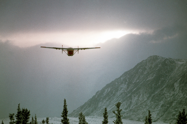 View of small aircraft flying low near snow covered landscape. Exact Date Shot Unknown