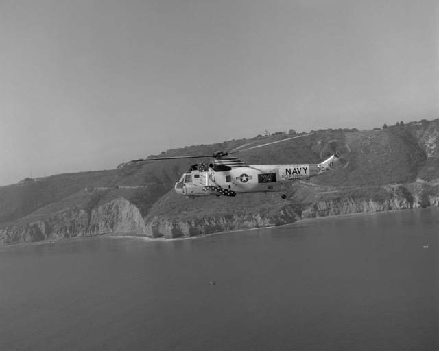 An air-to-air left side view of an SH-3D Sea King helicopter from Helicopter Anti-submarine Squadron 8 (HS-8) as it passes by Point Loma. The helicopter has a Bicentennial paint scheme