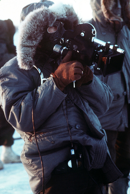 A cameraman films activities taking place during arctic training exercise Jack Frost '77