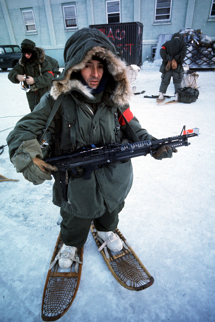 A soldier wears cold weather gear and snowshoes during arctic training exercise Jack Frost '77. He is armed with an M-60 machine gun