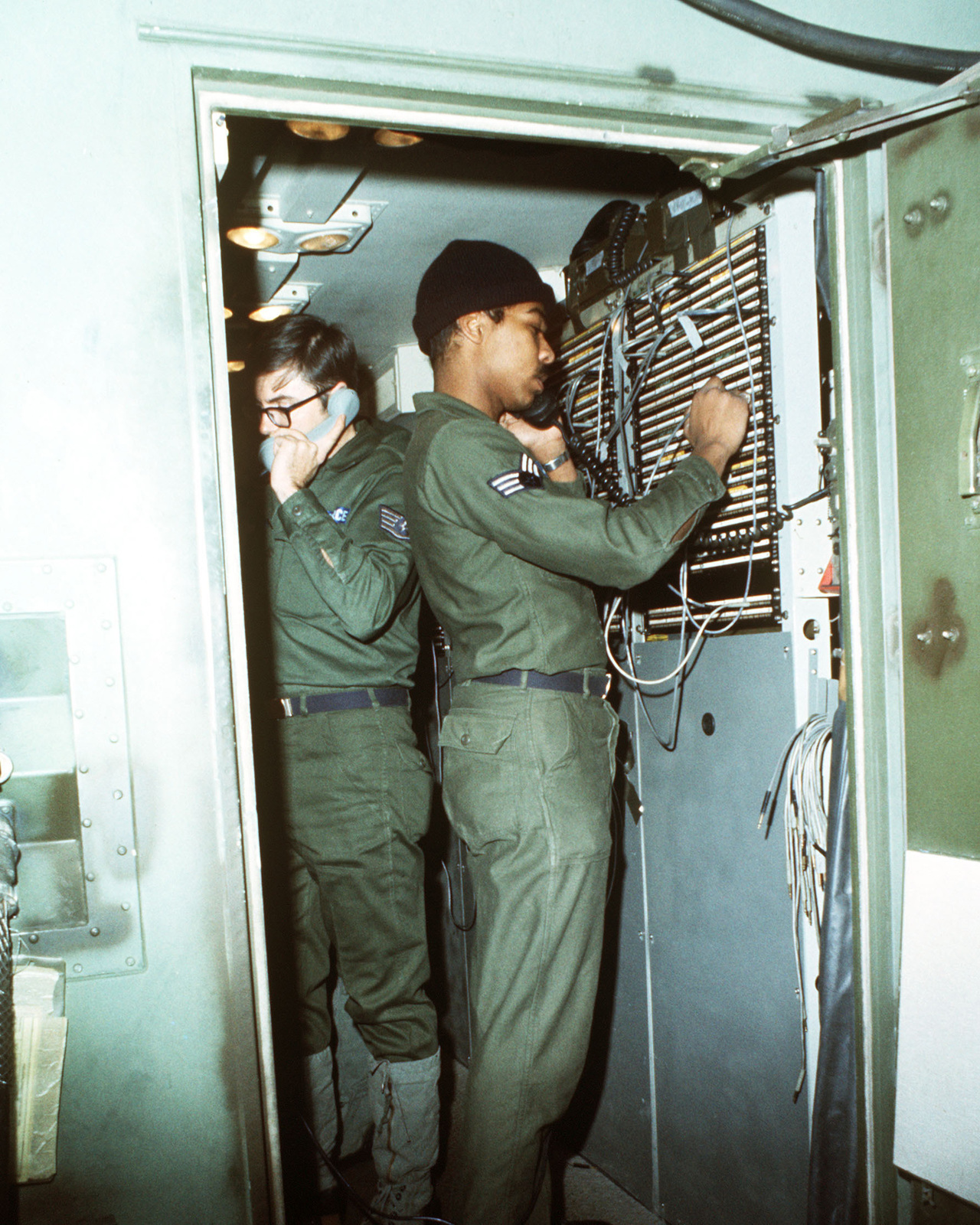 Air Force personnel work in the TSC-62 technical control central van during arctic training Exercise JACK FROST 77