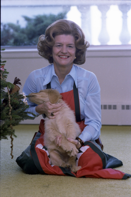 First Lady Betty Ford Holding Misty While the Puppy Attempts to Eat Christmas Tree Decorations