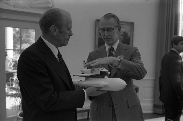 NASA Administrator Dr. James Fletcher Presenting a Model of the Space Shuttle Enterprise to President Gerald R. Ford in the Oval Office