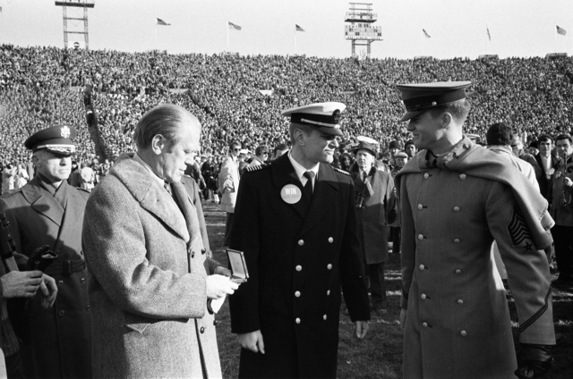 President Gerald R. Ford Admires a Gift Given to Him By Commander of Midshipmen James Adams and Captain of Corps of Cadets James Abcouwer While Crossing the Field at Halftime during the 75th Army-Navy Football Game at John F. Kennedy Stadium