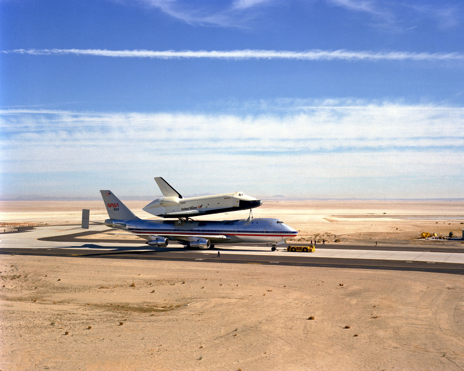 A right side view of the Space Shuttle Orbiter Enterprise and its specially-modified 747 transport aircraft being towed to the Weight and Thrust Hangar for vibration testing