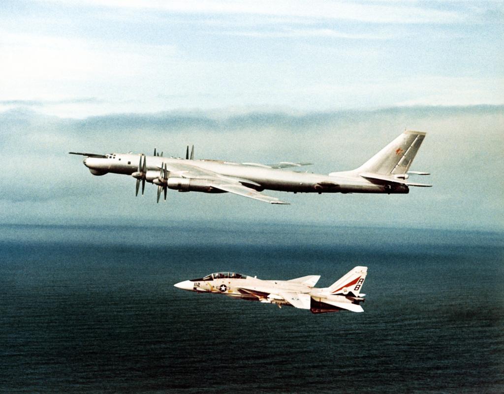 An air-to-air left side view of a Soviet Tu-95 Bear A/B aircraft as an F-14 Tomcat aircraft intercepts it
