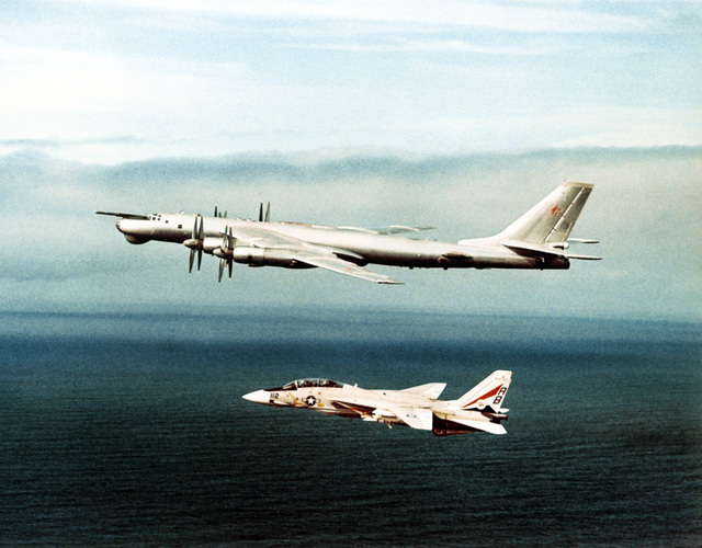 An air-to-air left side view of a Soviet Tu-95 Bear A/B aircraft as an F-14 Tomcat aircraft intercepts it