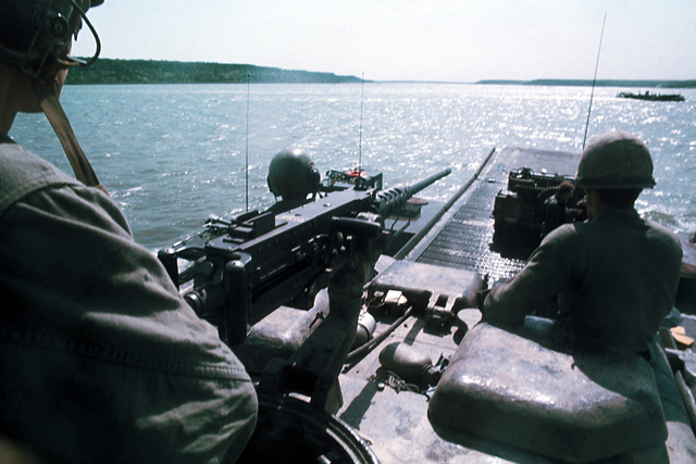 A soldier watches for the enemy as his M88 recovery vehicle, armed with an M60 machine gun, is ferried across the Cowhouse River during the joint services Operation GALLANT CREW '77