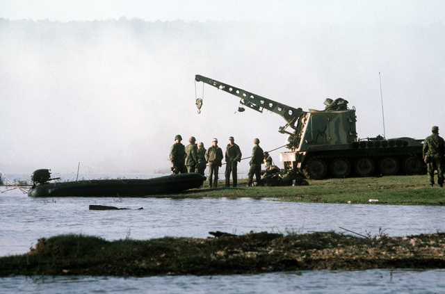 Members of the 86th Engineer Detachment stand near an M-578 armored recovery vehicle as lines are attached to a partially submerged armored personnel carrier (APC) (not visible) during recovery operations. The APC sank while crossing the Cowhouse River during the joint services Operation Gallant Crew `77