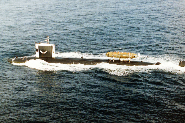 "An aerial port beam view of the nuclear-powered attack submarine USS PINTADO (SSN 672) underway while conducting submarine operations off the coast of San Diego. Mounted near the stern is the deep submergence rescue vehicle (DSRV-1) ""Mystic"", which can provide world-wide, rapid-deployment, all-weather capability for the rescue of survivors of a disabled submarine"