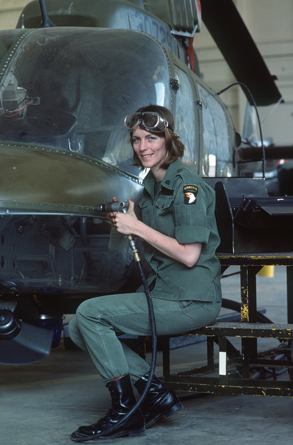 A female aircraft mechanic of the 101st Airborne Division services an OH-58 Kiowa helicopter