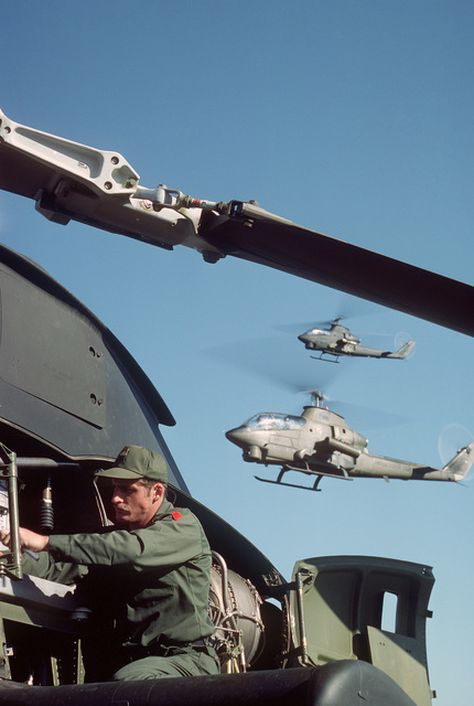 A US Army mechanic services an AH-1G Cobra helicopter while two AH-1Gs pass overhead