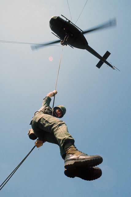 A US Army soldier rappels from a UH-1 Iroquois helicopter during a training exercise