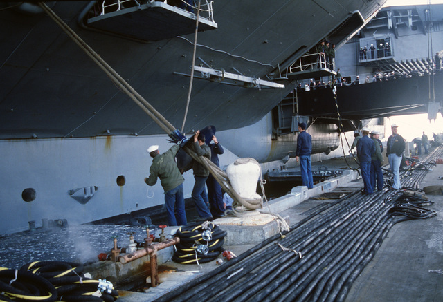 Sailors remove a rat guard from a mooring line as the aircraft carrier USS AMERICA (CV 66) prepares to leave port