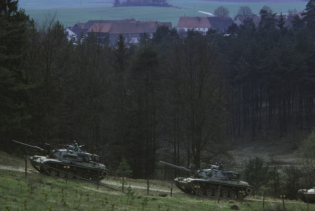 US Army M60 main battle tanks move along a dirt road during a field training exercise