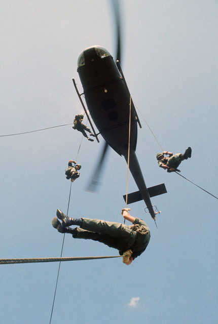 US Army soldiers rappel from a UH-1 Iroquois helicopter during a training exercise