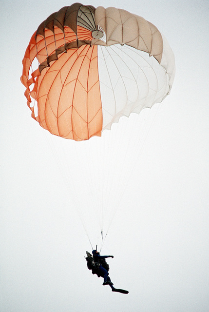 A pararescueman from the 129th Aerospace Rescue and Recovery Group of the Air National Guard drops into the ocean off the coast of California during a practice rescue mission
