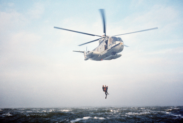 A sea-to-air view of an HH-3 Jolly Green Giant helicopter using a recovery hoist to lift two pararescuemen from the water off the coast of California. The men, from the 129th Aerospace Rescue and Recovery Group of the Air National Guard, are participating in a practice rescue mission