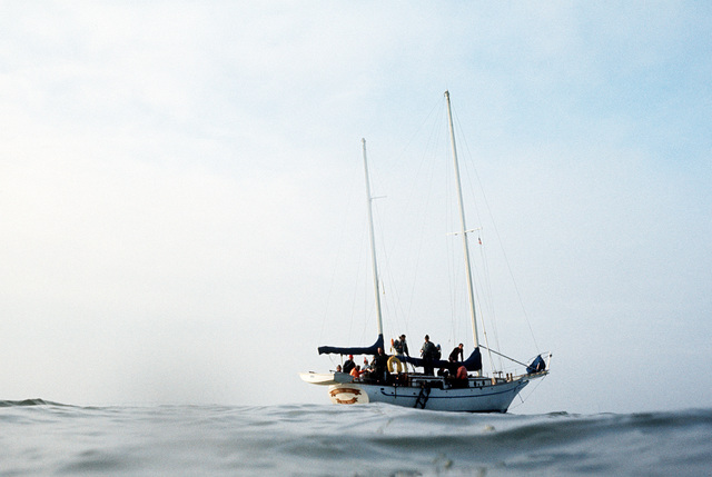 A starboard quarter view of a 30-foot long sailboat off the coast of California. The boat is the object of a practice rescue mission being conducted by the 129th Aerospace Rescue and Recovery Group of the Air National Guard