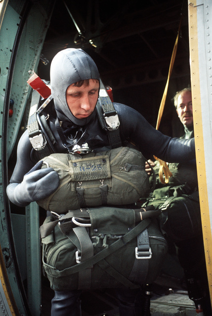 SGT Boyle, a pararescueman with the 129th Aerospace Rescue and Recovery Group of the Air National Guard, prepares to jump from the troop door of an RC-130 Hercules aircraft during a practice rescue mission off the coast of California