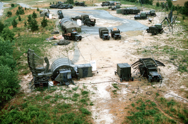 A mobile radar installation is set up during joint readiness training exercise SOLID SHIELD '77. One truck-mounted AN/TPS-43 tactical 3-D radar antenna is already up (lower left) while another is partially assembled (lower right)